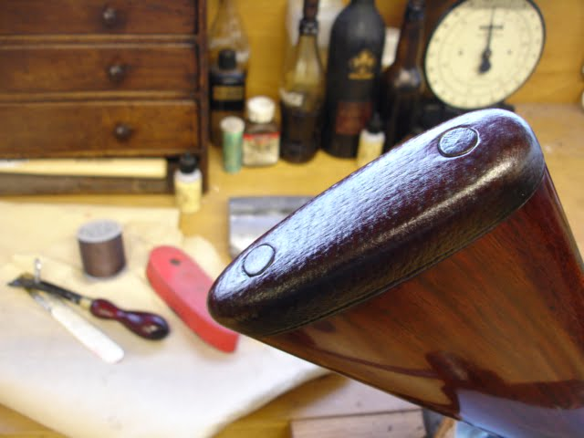 A leather-covered recoil pad fitted on a stock.